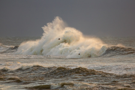 breaking wave: Rough sea with big breaking wave against rocks in a stormy evening Stock Photo