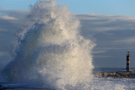 Detailed photo of a big breaking wave over a pier from the north of Portugal