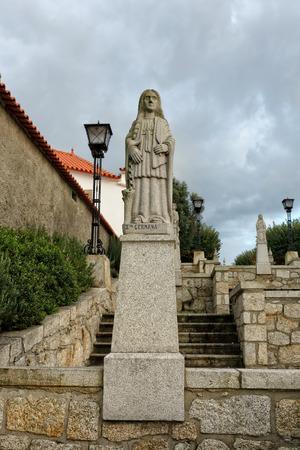 humilde: Esposende, Portugal - 28 de noviembre 2014: Granito estatua de Santa Germana, una de las hermanas de Santa Marinha (leyenda de los nueve santos hermanas), incluido en la escalera de Santa Marinha iglesia cat�lica, Forj�es, al norte de Portugal