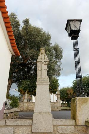 humilde: Esposende, Portugal - 28 de noviembre 2014: Granito estatua de Santa Liberata, una de las hermanas de Santa Marinha (leyenda de los nueve santos hermanas), incluido en la escalera de Santa Marinha iglesia católica, Forjães, al norte de Portugal