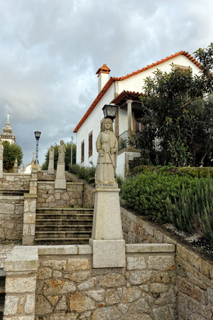 humilde: Esposende, Portugal - November 28, 2014: Granite statue of Santa Quiteria, one of the sisters of Santa Marinha (legend of the nine holy sisters), included in the staircase of Santa Marinha catholic church, Forjaes, north of Portugal Foto de archivo