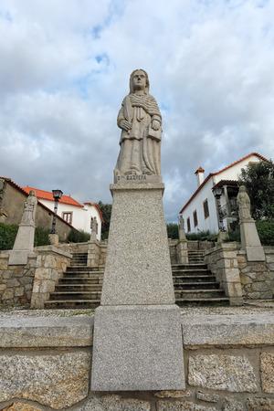 humilde: Esposende, Portugal - 28 de noviembre 2014: Granito estatua de Santa Bazilia, una de las hermanas de Santa Marinha (leyenda de los nueve santos hermanas), incluido en la escalera de Santa Marinha iglesia católica, Forjães, al norte de Portugal Editorial