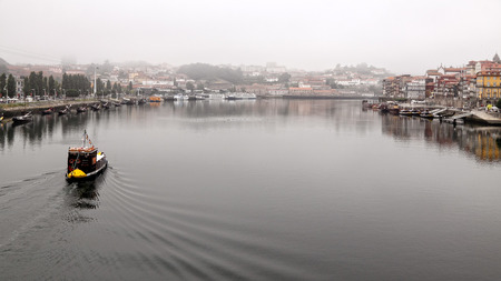 rabelo: Porto, Portugal - August 18, 2013: Small cruise ship, rabelo type, passing along the Gaia quay and Ribeira, toward the mouth of the Douro river, north of Portugal, in the typical morning mist.
