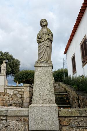 humilde: Esposende, Portugal - 28 de noviembre 2014: Granito estatua de Santa Marciana, una de las hermanas de Santa Marinha (leyenda de los nueve santos hermanas), incluido en la escalera de Santa Marinha iglesia católica, Forjães, al norte de Portugal