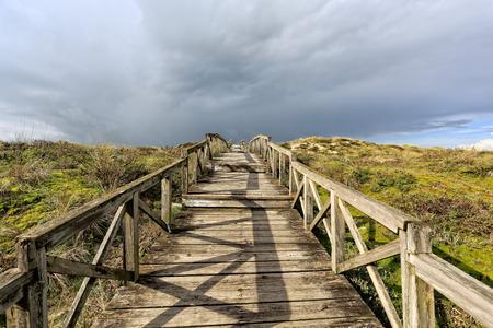 Sea coast dune with wooden walkway, north of Portugal Фото со стока