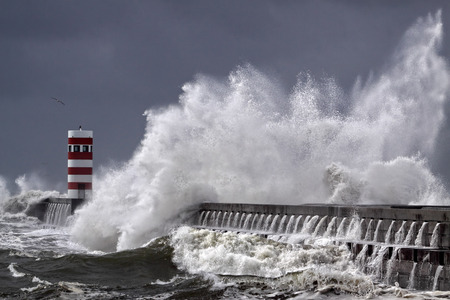 sea port: Winter storm with big waves and dark sky at the mouth of the River Douro, Porto, Portugal