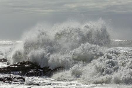 crashing: Big crashing wave against a rocky beach Stock Photo