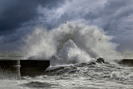 Big stormy waves against pier from the north of Portugal. Enhanced sky.