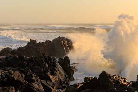Sea storm at sunset with big waves against cliff