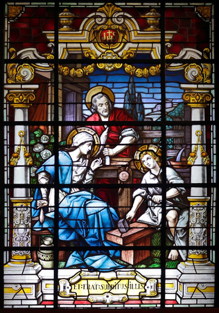 Porto, Portugal - March 23, 2015: Stained glass window from  church of Lapa representing a scene of the holy family, seeing Jesus learning carpentry, the office of the adoptive father, St. Joseph