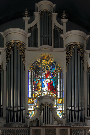 pipe organ: Porto, Portugal - March 23, 2015: Stained glass window from Lapa church behind the beautiful pipe organ in the choir