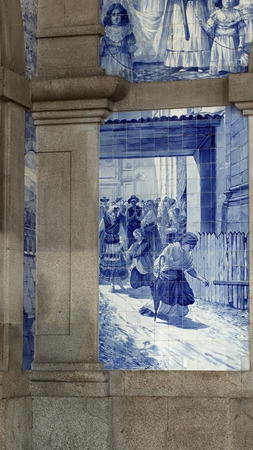 fulfilling: Porto, Portugal - March 23, 2015: Sao Bento railway station with famous tiles, installed in 1905. This panel represents a scene of a religious pilgrimage from the north of Portugal, sec XIX,  with a woman fulfilling a knee promise in the foreground