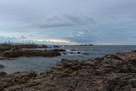 powerplant: Rocky sea coast with an oil refinery and powerplant on the horizon