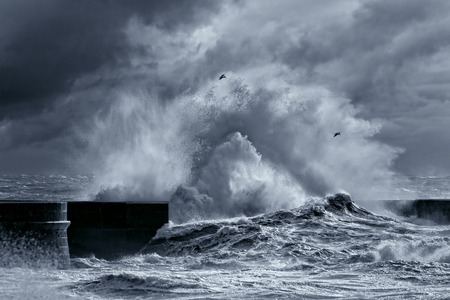 Big stormy waves against pier from the north of Portugal. Enhanced sky. Black and white toned blue.