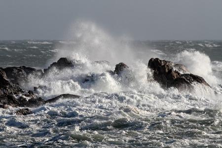 crashing: Big waves crashing against rocks in a windy afternoon