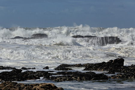 breaking in: Big white waves breaking in a rocky beach from the north of Portugal