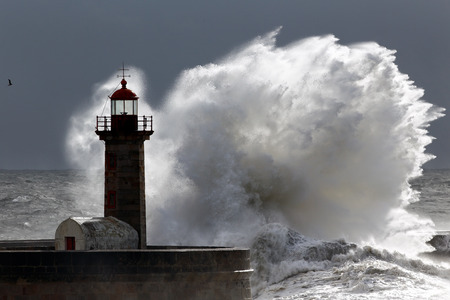 lighthouses: Backlit big stormy wave over lighthouse