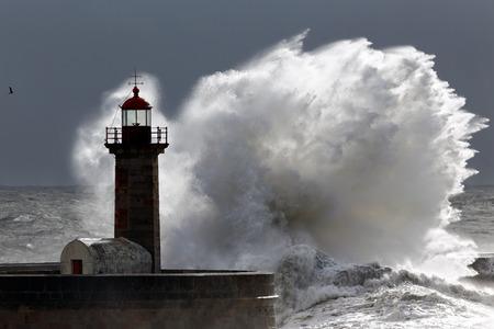 Backlit big stormy wave over lighthouse