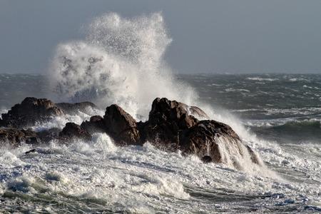 granola: Grandes olas rompiendo contra las rocas en una tarde ventosa