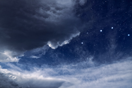Cloudy night with holes in the clouds revealing the stars