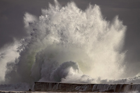 breaking wave: Huge Atlantic stormy breaking wave against pier and beacon of river Ave mouth, Vila do Conde, north of Portugal