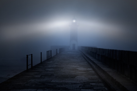River mouth lighthouse and granite pier in a foggy night