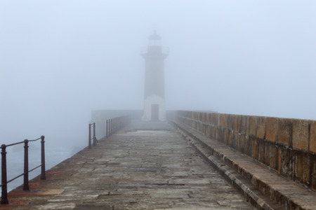 Old lighthouse and pier in a foggy early morning Stock Photo