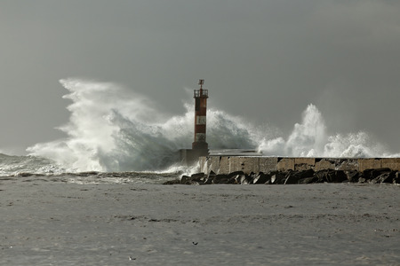 granola: Winter stormy seascape from the north of Portugal with big waves over beacon and pier. Ave river mouth, Vila do Conde.