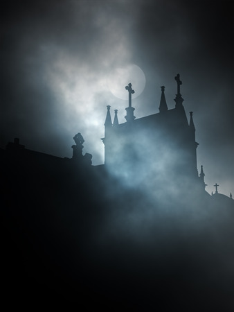 Backlit old cemetery in a foggy full moon night