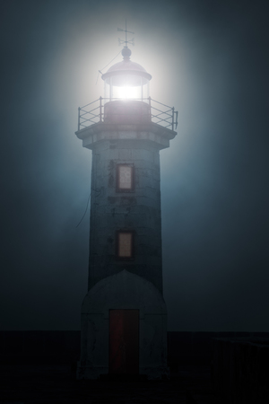 lighthouse with beam: River mouth lighthouse and granite pier in a foggy night