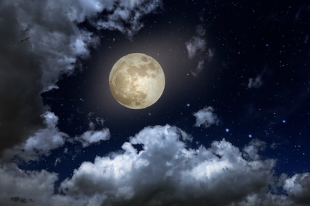 Full moon in a starry night with some clouds