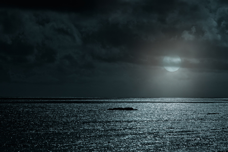 Glistening sea in a cloudy full moon night