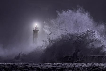 voile: Embouchure de la rivière phare voyant grosse vague de la mer orageuse de nuit