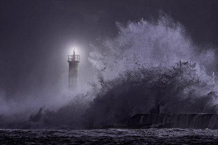 storms: River mouth lighthouse seeing big stormy sea wave at night