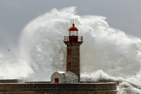 granola: Big stormy waves over old lighthouse and pier of Douro mouth harbor, Porto, Portugal. Foto de archivo