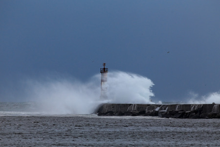 conde: Big stormy waves against pier and beacon of Ave river, Vila do Conde, Portugal, in a clear blue sky evening Stock Photo