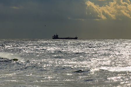 glistening: Commercial ship on the horizon of a glistening sea before rain and storm