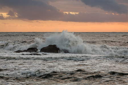 breaking waves: Breaking waves over rocks at sunset. Portuguese north coast. Stock Photo