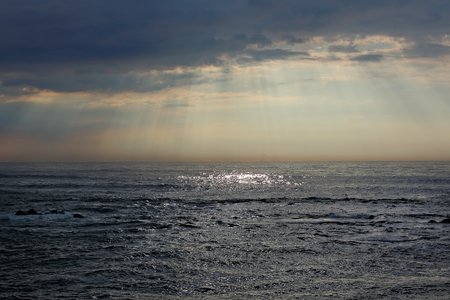 glistening: Early spring cloudy seascape before storm seeing natural sunbeams and glistening sea at sunset. Northern portuguese coast.