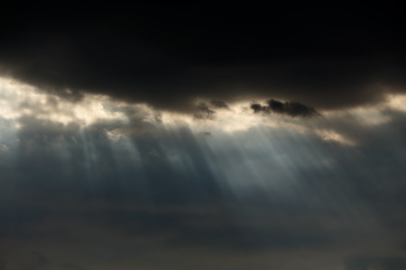 dark sky: Early spring cloudy sky with natural sunbeams