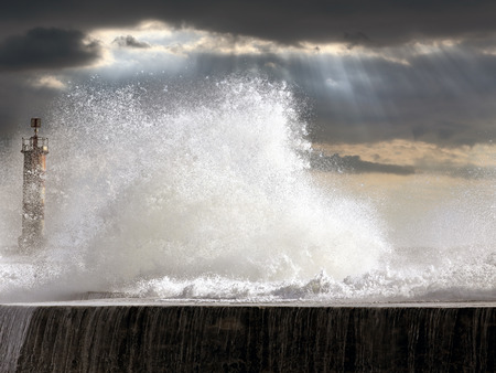 enhanced: Stormy seascape at sunset with big splashing waves over pier and beacon. North of Portugal. Enhanced sky.
