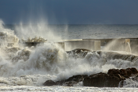 hurricane weather: Detailed breaking stormy waves over rocks and pier from nort of Portugal Stock Photo