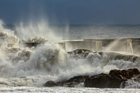 clima: tormentosas olas rompientes detalladas sobre las rocas y el muelle de Nort de Portugal Foto de archivo