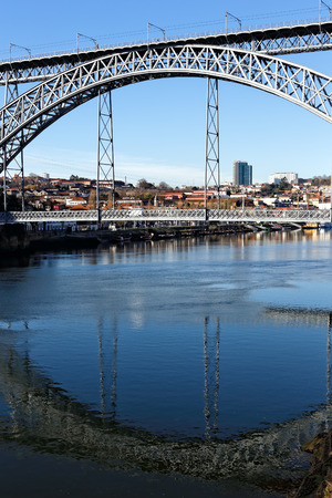 luis: Porto, Portugal - March 4, 2015: Famous old iron Dom Luis Bridge. Vertival view with reflection on the river
