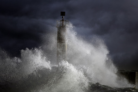 Big Atlantic stormy waves over lighthouse. North of Portugal. Enhanced sky Stock Photo