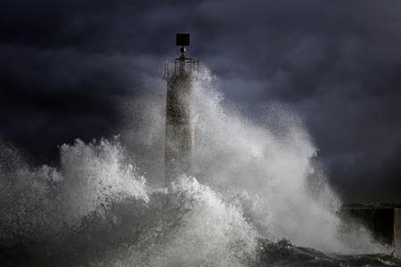 enhanced: Big Atlantic stormy waves over lighthouse. North of Portugal. Enhanced sky Stock Photo