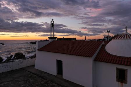 conde: Old medieval chapel (eleventh century) of Nossa Senhora da Guia, near the sea, in the evening. Vila do Conde, north of Portugal.