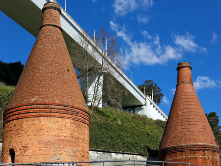 industrial heritage: Ancient furnaces with chimneys in brick, from the beginning of the twentieth century, belonging to a disabled ceramic factory , located beneath the new railway bridge of St. John. Oporto industrial archaeological heritage. Stock Photo