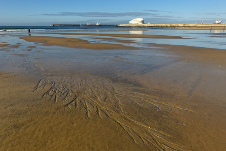 sand harbor: Matosinhos peaceful beach at low tide on a bright morning with interesting sand ripples in the foreground and the south of Leixoes harbor in background seeing the new and dashing white passenger terminal. Focus on the foregroud.