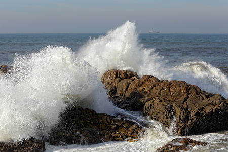 Splashing waves against rocks from the northern portuguese coast in a beautiful sunny autumn morning